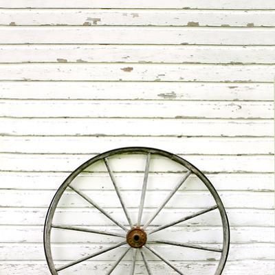Antique Wooden Wagon Wheel on Rustic White Background by Christin Lola