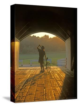 Bicyclist at Covered Bridge, Iowa, USA