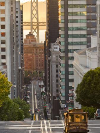 Cable Car Crossing California Street With Bay Bridge Backdrop in San Francisco, California, USA