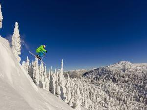 Jumping from Cliff on a Sunny Day at Whitefish Mountain Resort, Montana, Usa by Chuck Haney