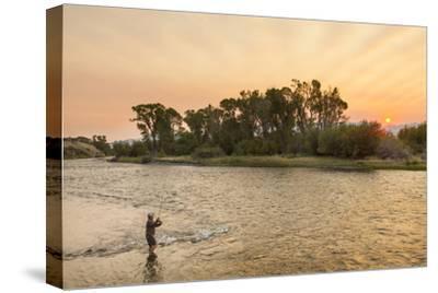 Reid Sabin Fly Fishing at Sunrise on the Madison River Near Ennis, Montana, USA