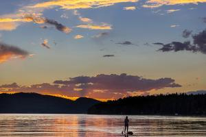 Standup Paddleboarder Silhouetted by Sunset, Whitefish Lake, Montana by Chuck Haney