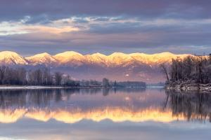 Swan Mountains Reflect into the Flathead River, Sunset, Montana, USA by Chuck Haney