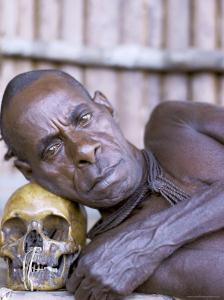 Portrait of an Asmat Tribesman Leaning on a Human Skull, Irian Jaya, Indonesia by Claire Leimbach