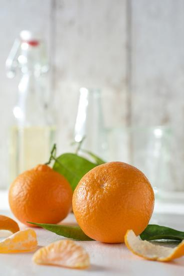Clementines with Foliage, Pieces of Clementines and Peel in Front of Bright Background-Jana Ihle-Photographic Print