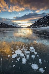 Frozen gas bubbles trapped in the ice at sunset. Silvaplana Lake, Silvaplana, Engadin, Graubunden, by ClickAlps