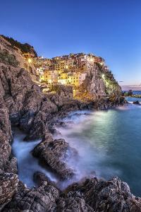 Manarola Village Illuminated by the Blue Light of Dusk with its Typical Pastel Colored Houses by ClickAlps
