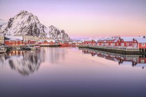 Pink Sunset over the Typical Red Houses Reflected in the Sea. Svollvaer, Lofoten Islands, Norway by ClickAlps
