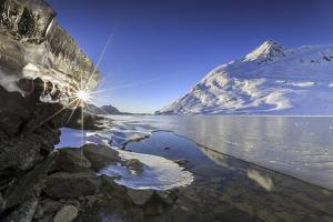 The Sun Shining Through Icicles on the Shores of Lake Bianco, Canton of Graubunden. Engadine by ClickAlps