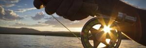 A Sunset Sunstart Through the Fly Reel of an Angler on the Henry's Fork River in Idaho. by Clint Losee