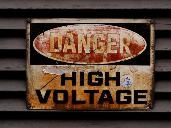 Close-up of a Faded Red and Black and White High Voltage Sign--Photographic Print