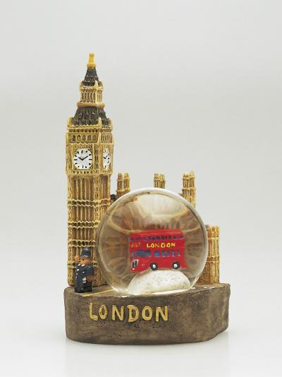 Close-Up of a Toy Bus in a Snow Globe in Front of a Figurine of a Clock Tower--Photographic Print