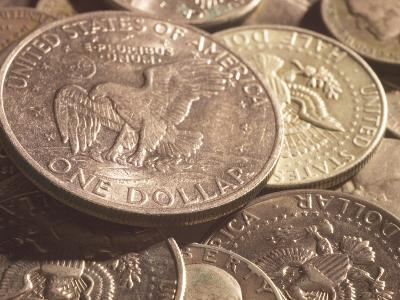 Close-Up of American Silver Dollar Coin with Eagle on its Face with Other Coins--Photographic Print