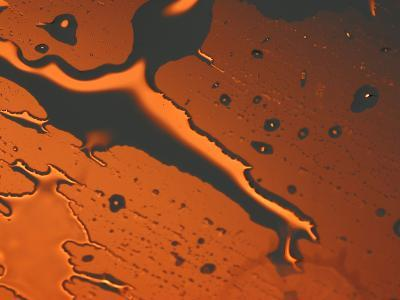 Close-up of Illuminated Orange Water Droplets and a Puddle on a Shiny Surface--Photographic Print