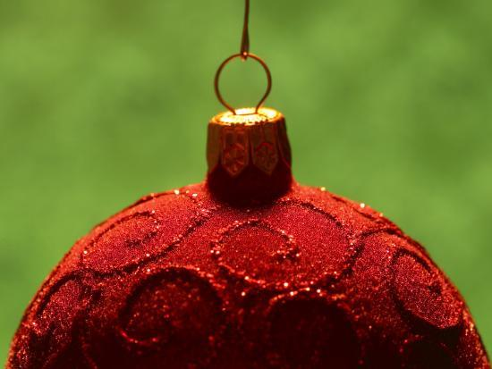Close-Up of Red Christmas Decoration with Glitter Pattern Against Green Background--Photographic Print