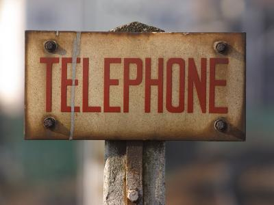 Close-Up of Singed Telephone Sign Outdoors--Photographic Print