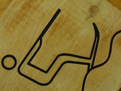 Close-Up of Wooden Tile with Water Skiing Figure--Photographic Print