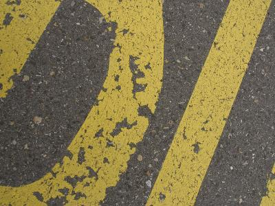 Close-up of Yellow Letters Painted on Gray Asphalt--Photographic Print