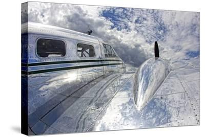 Clouds and Sky Reflecting Off the Shiny Silver Surface of An Airplane-Robbie George-Stretched Canvas Print
