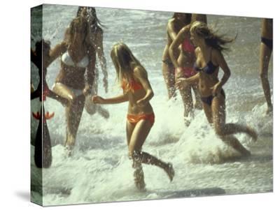Bikini Clad Teens Frolicking in Surf at Beach