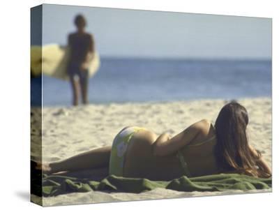 Seen from Her Back, Young Woman Lying on Beach Wearing Bikini Viewing Ocean
