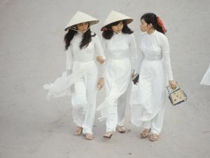 Three Vietnamese Young Women in White Fashion Walking Down the Street by Co Rentmeester