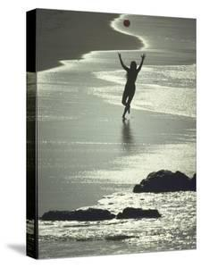 Young Woman in Silhouette Running Along Beach at Twilight Throwing Beach Ball Up in the Air by Co Rentmeester