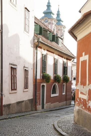 Cobblestone Street and Narrow Buildings with Church Towers in Background, Eger, Hungary-Kimberly Walker-Photographic Print