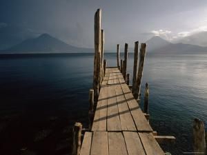 Wooden Jetty and Volcanoes in the Distance, Lago Atitlan (Lake Atitlan), Guatemala, Central America by Colin Brynn