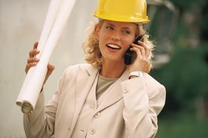 Woman in Hard Hat with Blueprints Talking on Cell Phone by Comstock