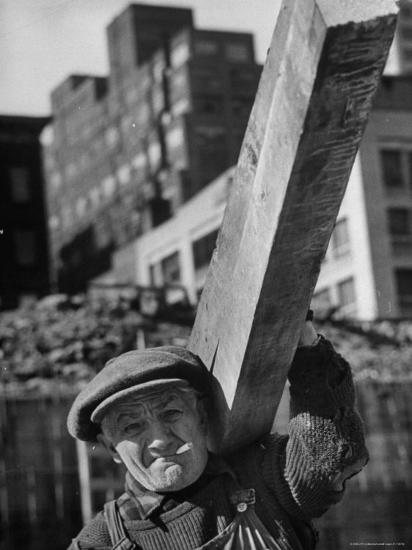 Construction Worker Carrying a Piece of Wood-Cornell Capa-Photographic Print