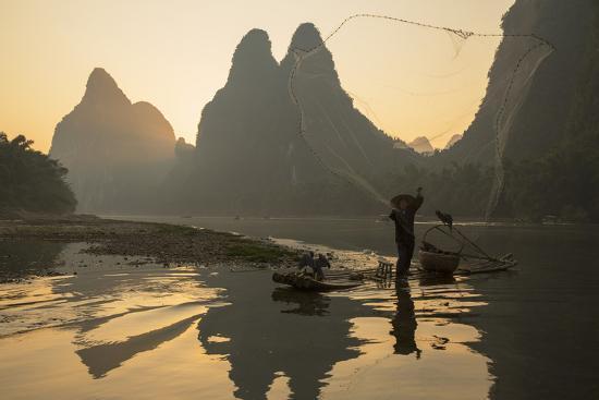 Cormorant Fisherman Throwing Net on Li River at Dawn, Xingping, Yangshuo, Guangxi, China-Ian Trower-Photographic Print