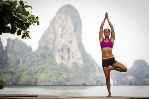 A Woman Doing Tree Pose Or Vrksasana by Cory Richards