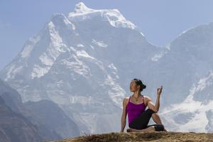 A Woman Practices a Half Spinal Twist Pose or Ardha Matsyendrasana by Cory Richards