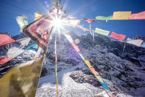 Buddhist prayer flags hang at Hkakabo Razi basecamp. by Cory Richards