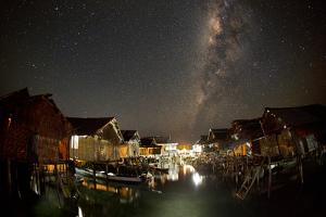 The Milky Way Stretches Above the Warm Glow of Sampela at Night by Cory Richards