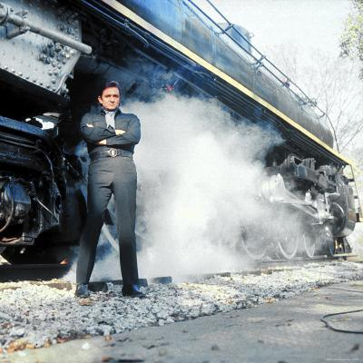 Country Music Star Johnny Cash Wearing Black Clothing and Standing in Front of a Locomotive-Michael Rougier-Premium Photographic Print