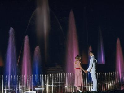 Couple Holding Hands Watches Water Fountains Illuminated at Night-B^ Anthony Stewart-Photographic Print