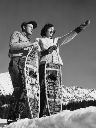Couple Holding Snowshoes, Woman Pointing--Photographic Print