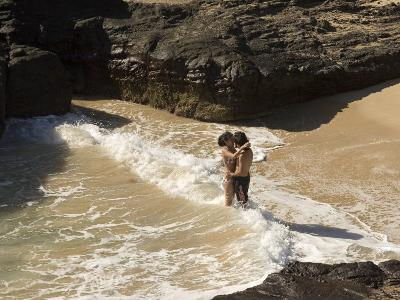 Couple Kissing in the Surf at Halona Beach on Oahu Island-Charles Kogod-Photographic Print