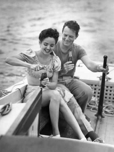 Couple on Small Sail-Boat Drinking Coke-George Marks-Photographic Print