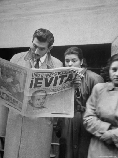 Couple Reading Newspaper Account of the Death of Evita Peron at 33 from Cancer-Alfred Eisenstaedt-Photographic Print