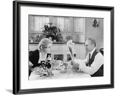 Couple Reading Newspaper at Breakfast Table--Framed Photo
