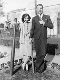 Couple Standing Together with One Oversized Baseball Bat