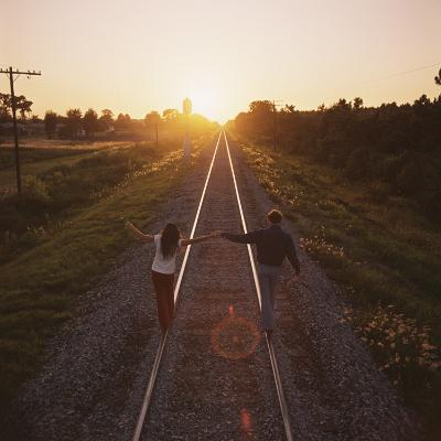 Couple Walking on Railroad Tracks Holding Hands-Dennis Hallinan-Photographic Print