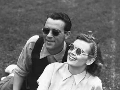 Couple Wearing Sunglasses Sitting on Grass, (B&W)-George Marks-Photographic Print