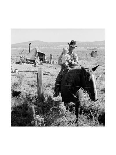 Cowboy Holds His Baby While Riding a Horse-Dorothea Lange-Art Print