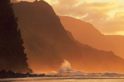 Crashing Waves Against a Mountain at Sunset--Photographic Print