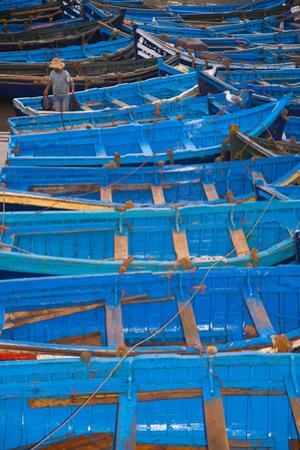 A Fisherman Stands in the Traditional Blue Boats of Essaouira Harbor