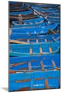 A Fisherman Stands in the Traditional Blue Boats of Essaouira Harbor by Cristina Mittermeier